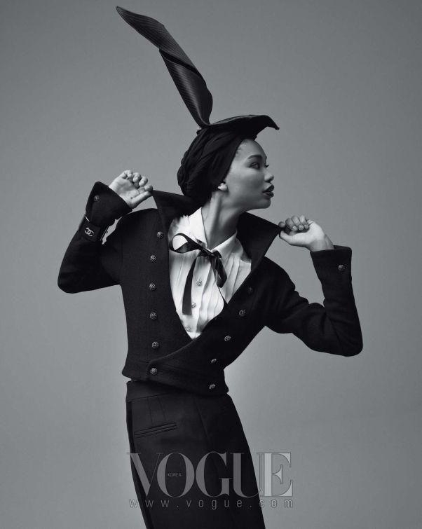 화이트 셔츠 블라우스와 더블 버튼의 블랙 턱시도 재킷과 롱 스커트, 뱅글은 모두 샤넬(Chanel).