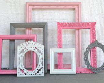 Pink, grey and white picture frames on an accent wall.
