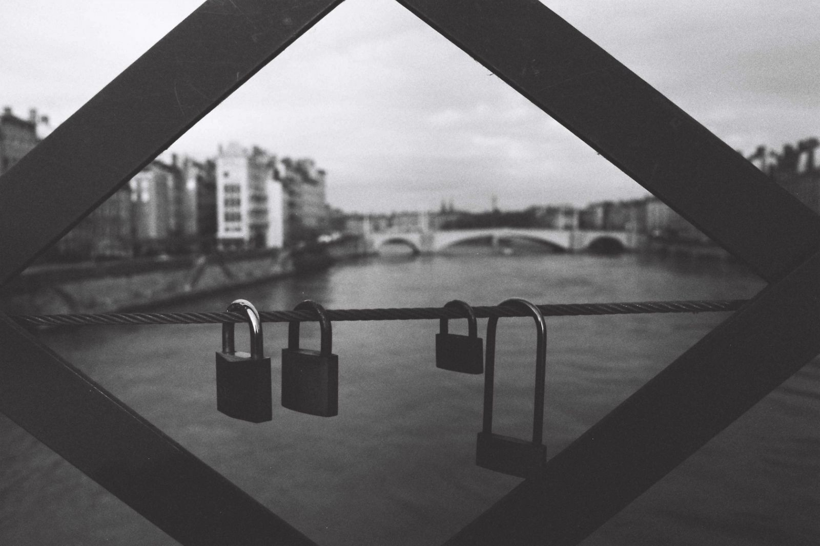 Four padlocks hanged on a bridge cable along the Saone river in Lyon, December 2014 | Credit: Ryan Burton