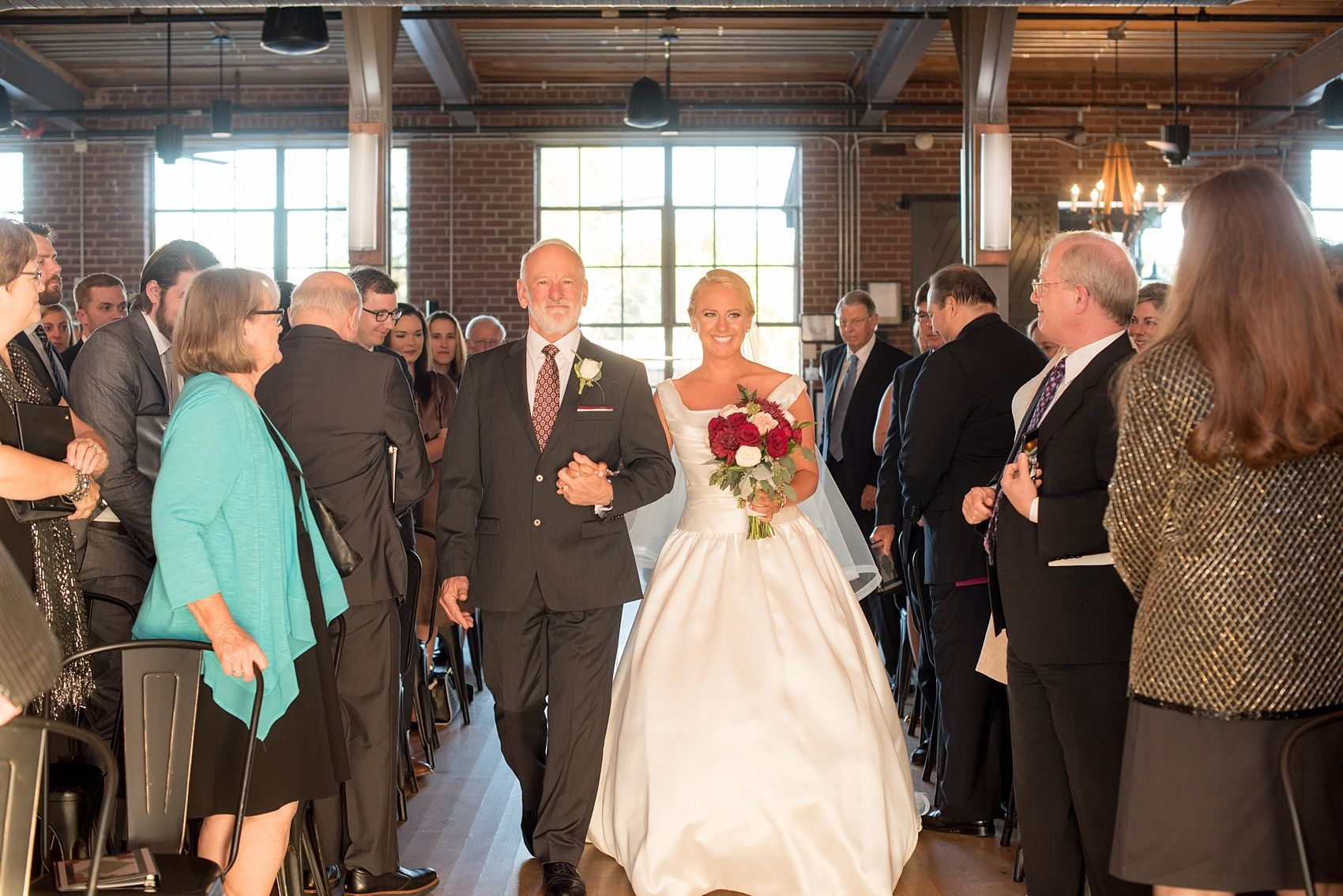 Mikkel Paige Photography photo of a wedding at The Rickhouse, Durham. A picture of the bride and her father walking down the aisle.