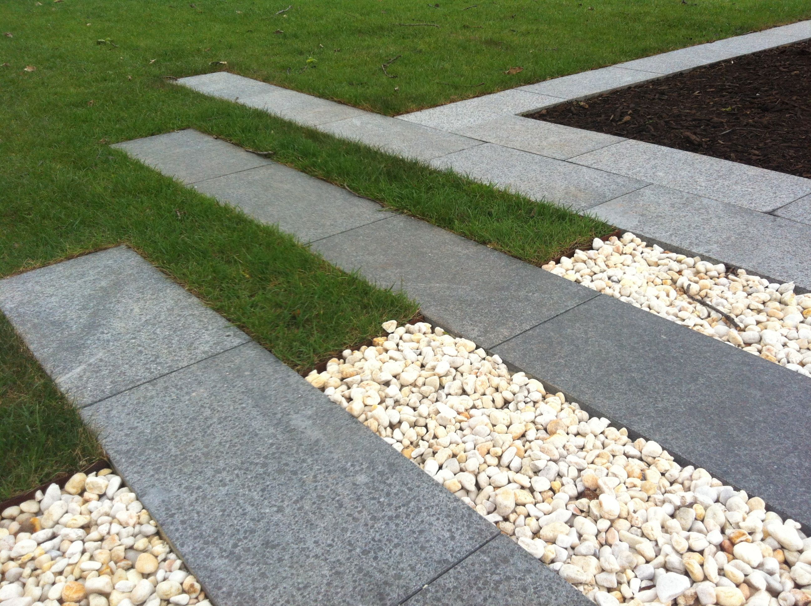Granite steppers interspersed with stone pebbles and lawn for Garden stepping stone designs