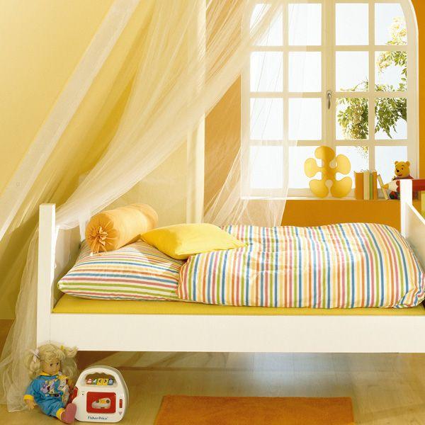 Ein kleiner orangefarbener Teppich unterm Bett sorgt morgens für ein angenehmes Aufstehen und warme Füße. Er spiegelt gleichzeitig das Orange der Wandfarbe wider.