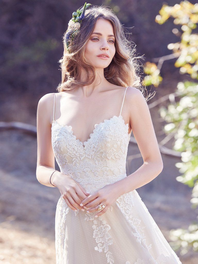 ce7b5edf93 EMILY, A chic A-line with unique details, this boho wedding dress features  horizontal lace motifs, scattered lace appliqués, and a striking lace hem  on ...