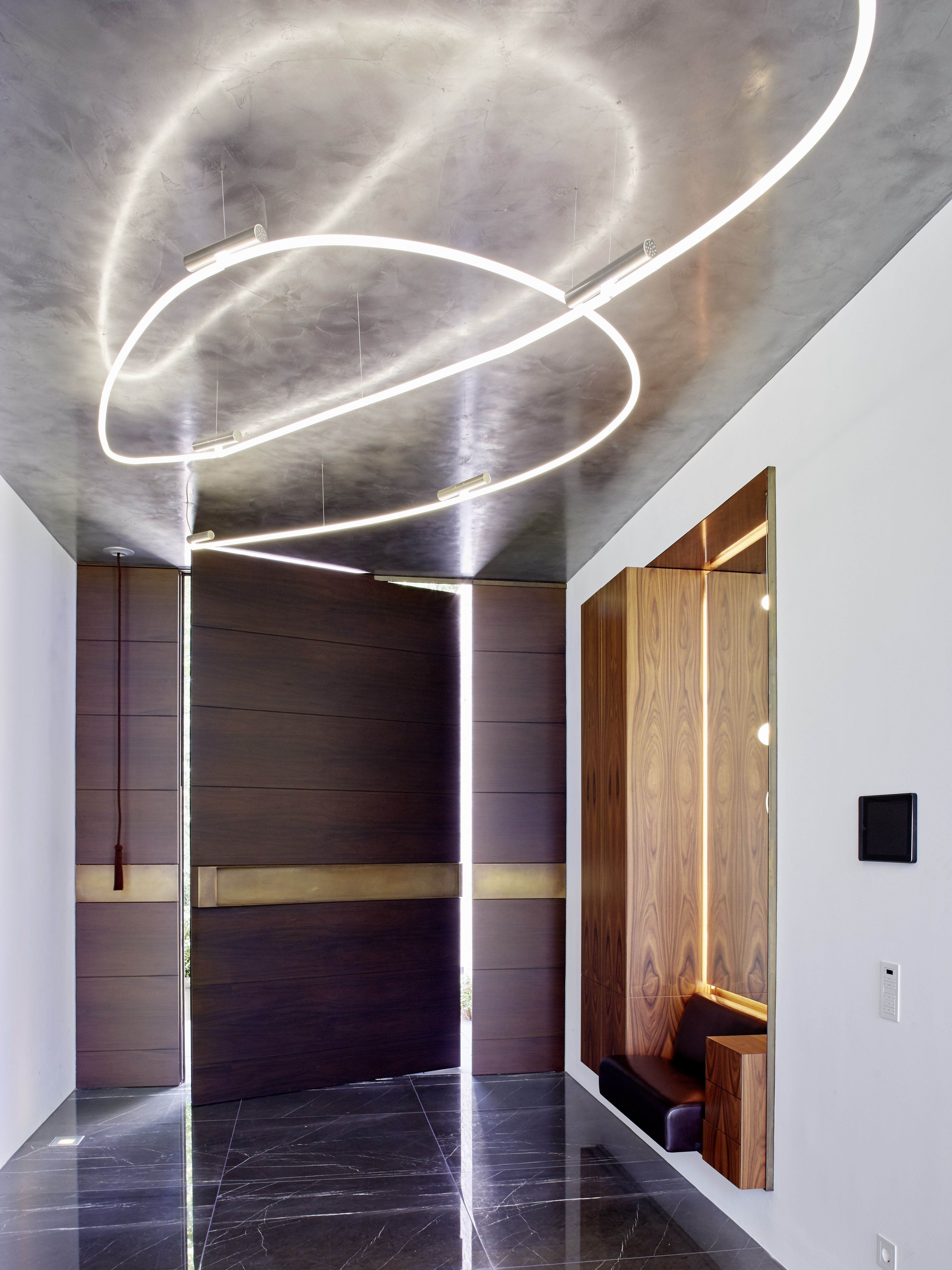 The entrance hall features a seventeen metre long neon chandelier'  suspended from a metallic-coated ceiling.
