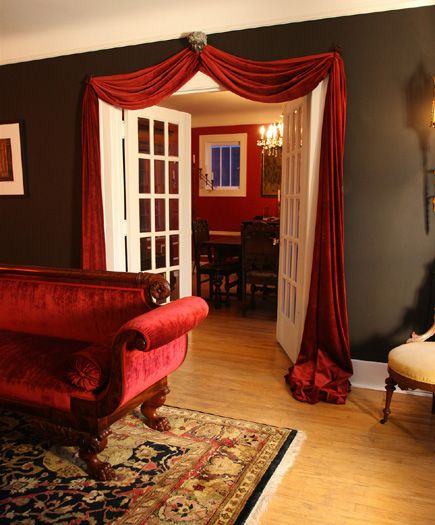 A Red Velvet Sofa And Matching Swag Over The French Doors Add