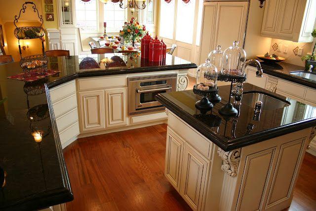 black counters, cream cabinets, wood floors. Love ...