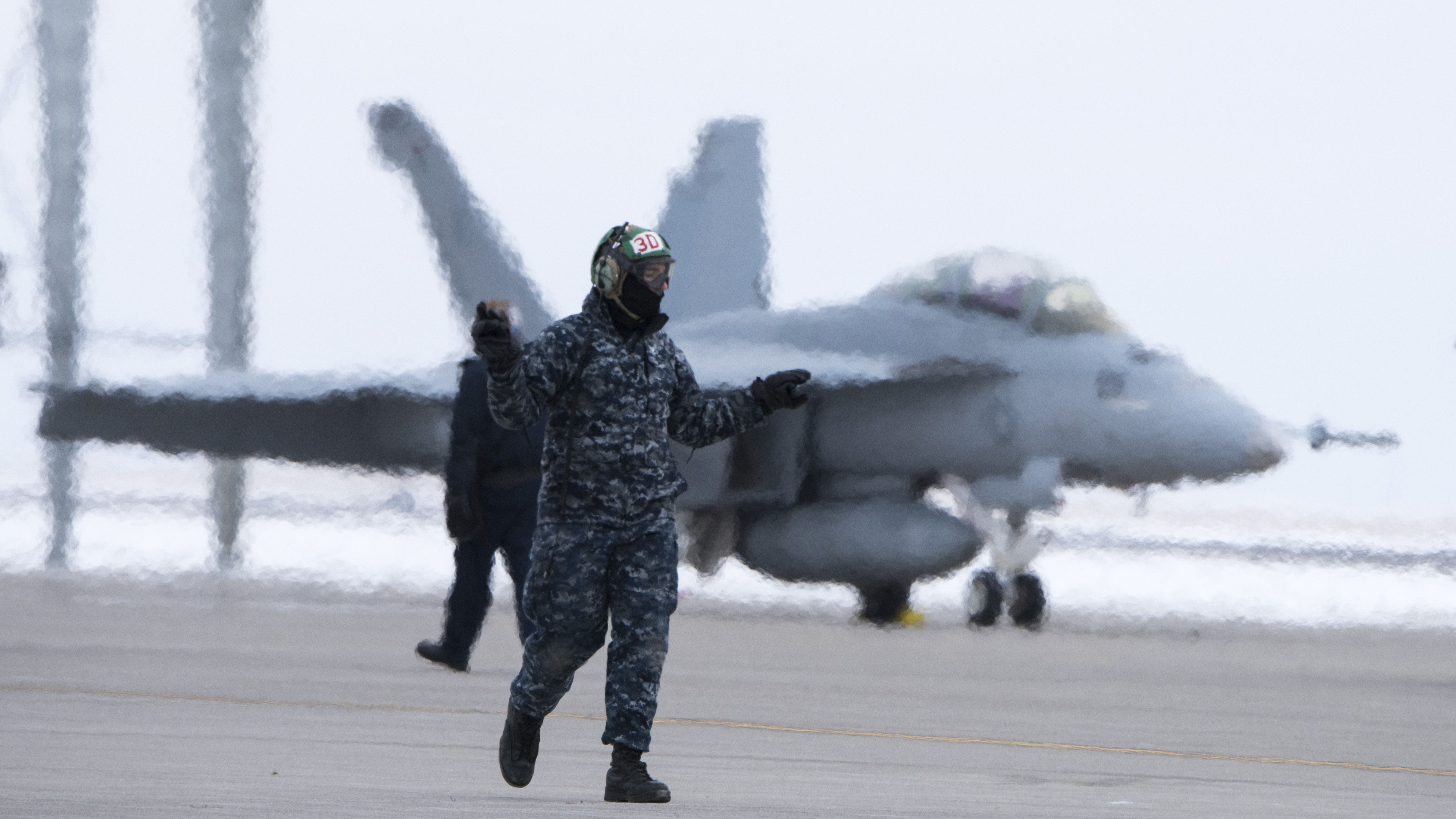 A U.S. Navy maintainer with Strike Fighter Squadron 106 marshals an F/A-18 Hornet out of a parking position on the flightline Dec. 2, 2015, at Mountain Home Air Force Base, Idaho. (U.S. Air Force photo by Senior Airman Jeremy L. Mosier/RELEASED)