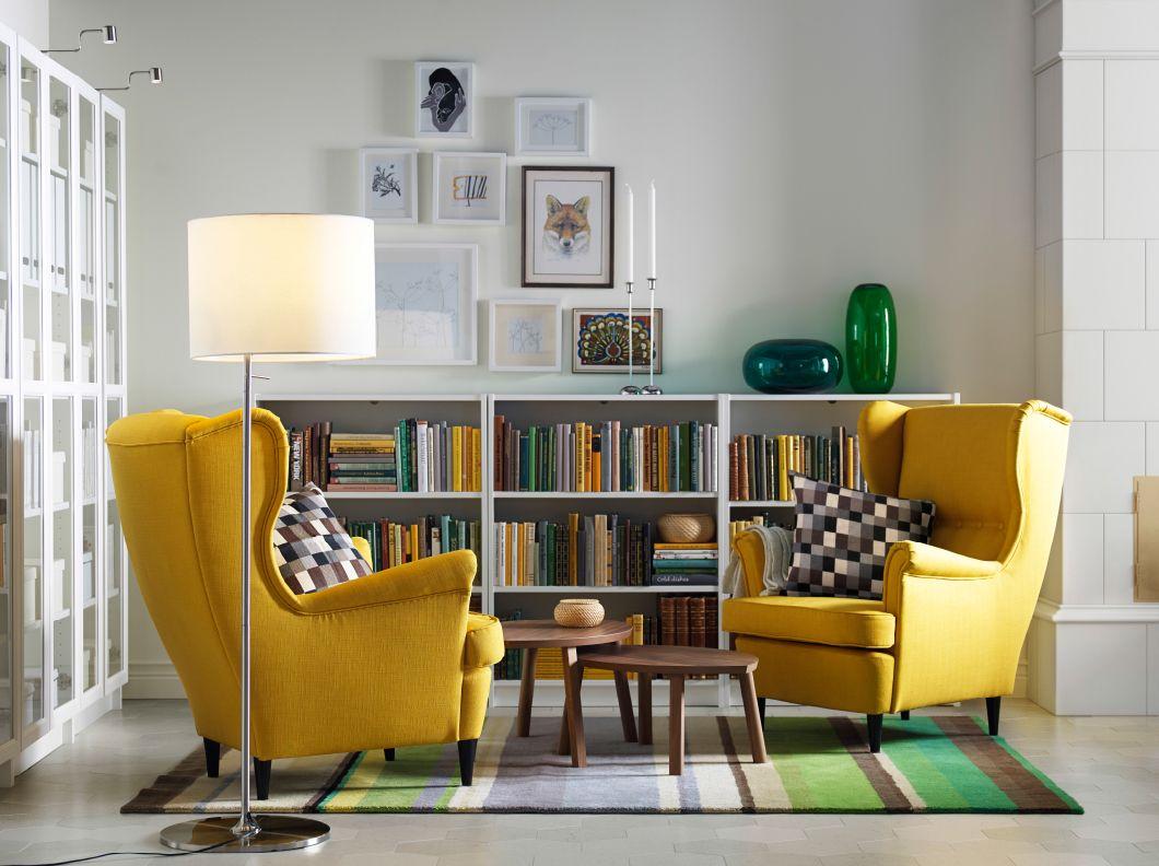 Lys stue med 2 gule øreklapstole, 2 indskudsborde af valnøddetræsfiner, hvide reoler og hvide vitrineskabe.