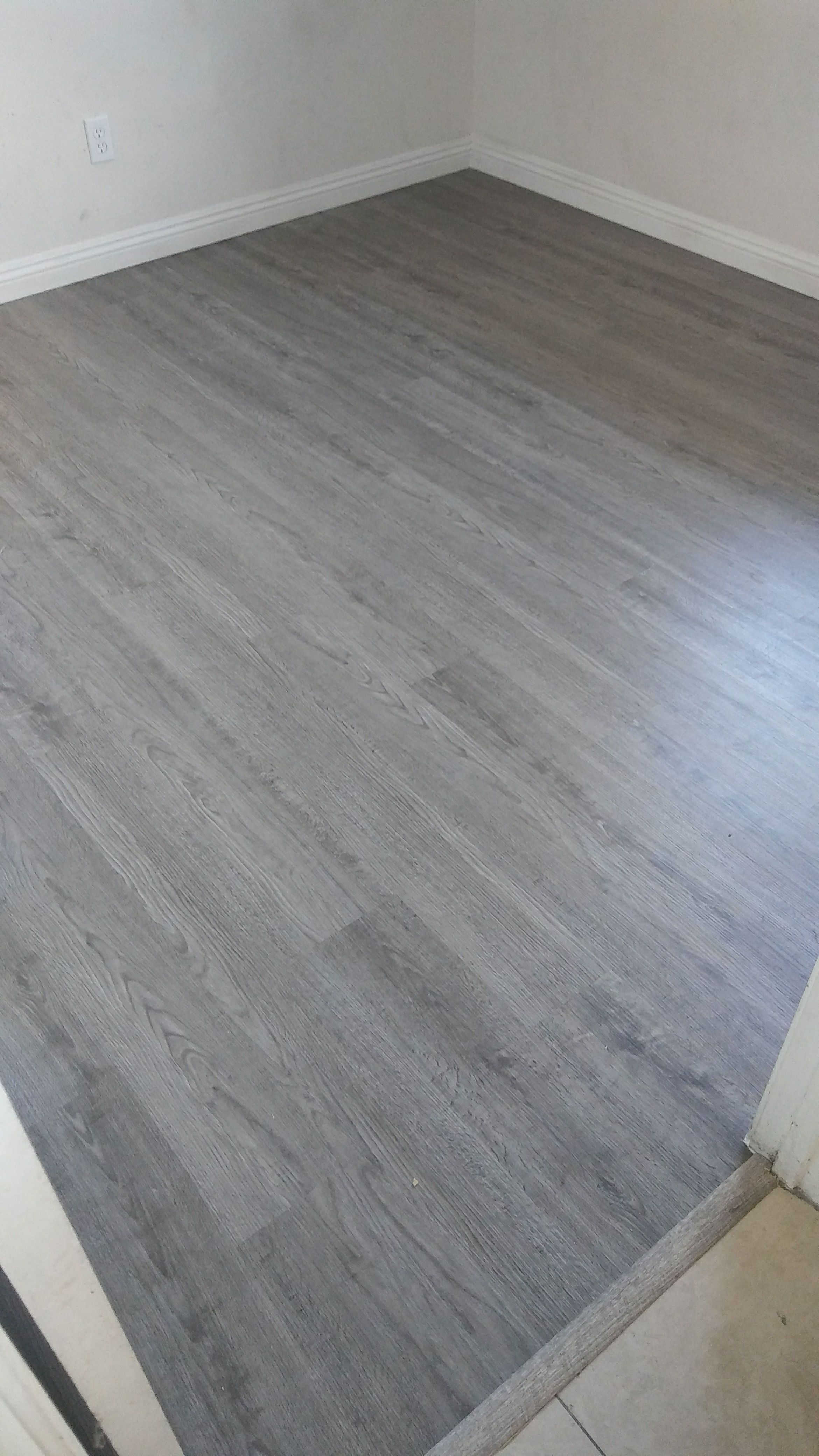 Before And After Photos Of A Plank Vinyl Installation In Midland Gray Color Flooring P Grey Vinyl Plank Flooring House Flooring Grey Wood Floors Living Room