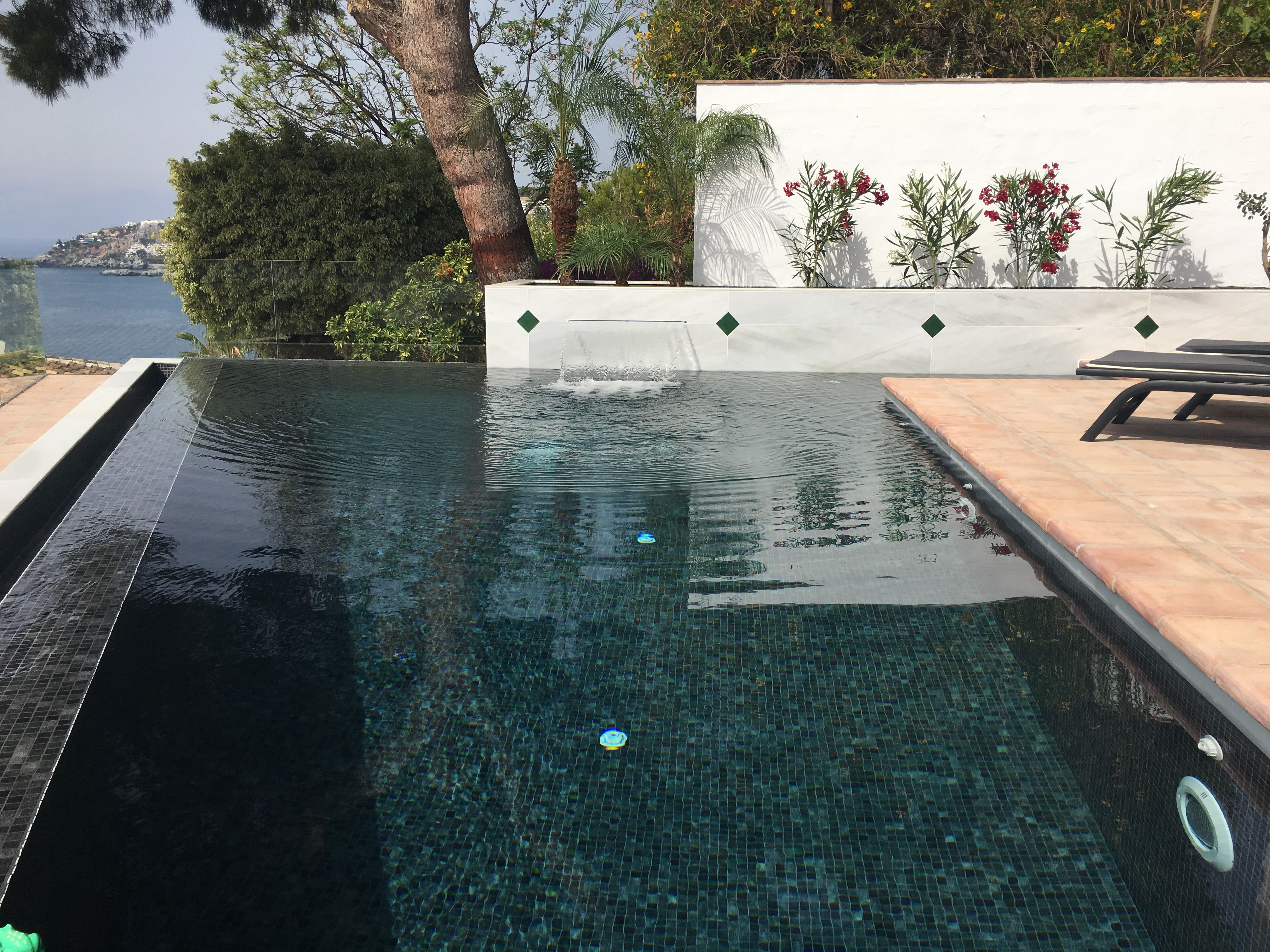 Piscina de borde rebosante con gresite negro infinity pool with