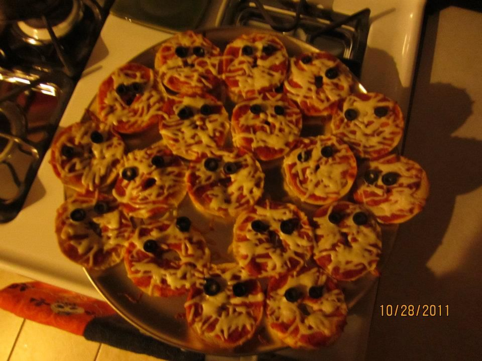 Pizza Mummies: Made with small bagels, pizza sauce, mozzarella cheese and black olives