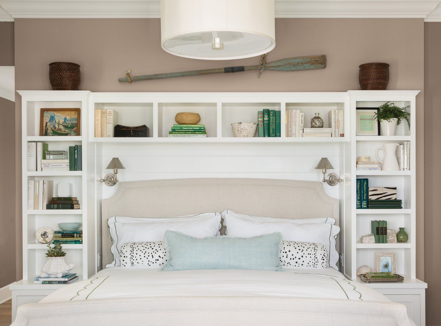 Creamy neutral walls enhance a beautiful storage headboard by complementing  the decorative items and echoing the