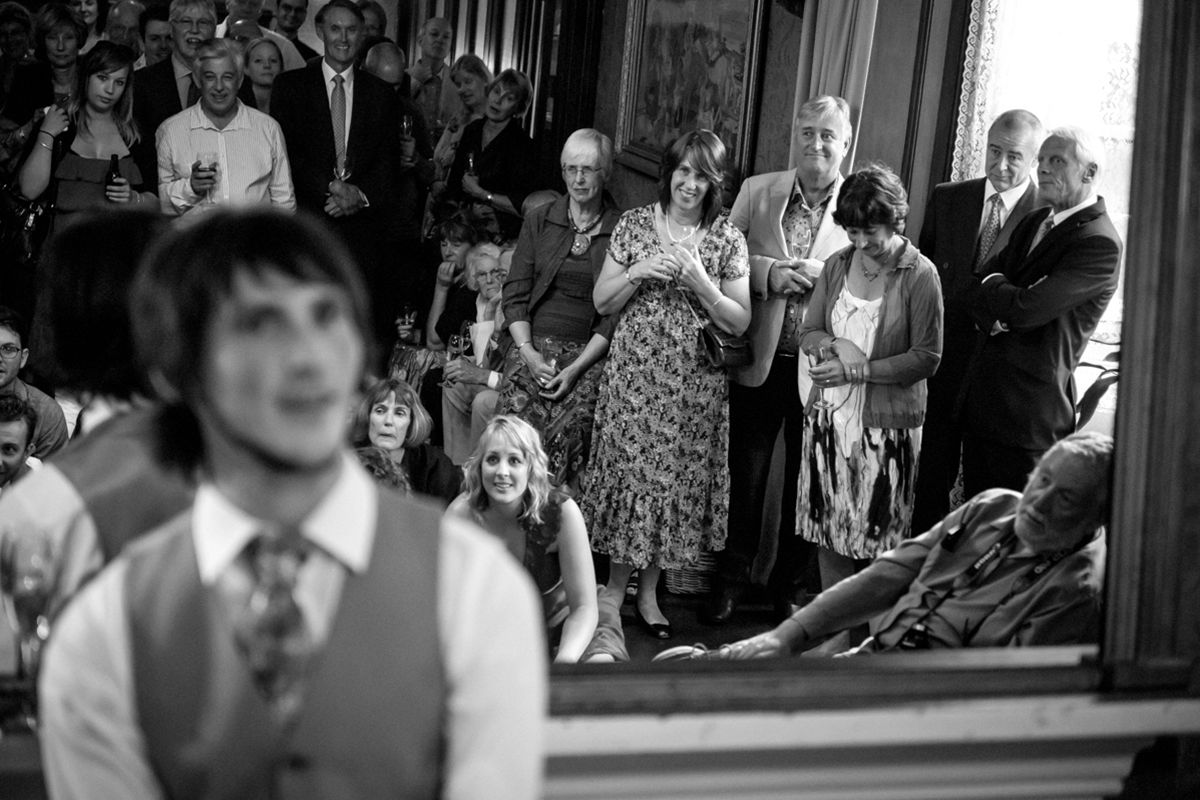 Reflection of the guests in a large mirror during speeches at a wedding at Alberton House, Mt Albert, Auckland. Black and white.  Love Images creates beguiling fine art bridal images for the most discerning clients. We specialise in natural and relaxed photojournalistic wedding photography, supplying the most exclusive albums and prints from manufacturers such as Cypress Albums, Queensberry and Couture Book. We are a high end studio located in the beautiful city of Auckland, New Zealand.