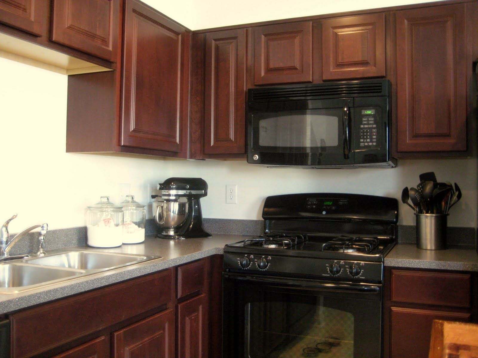 i like this look a lot! black appliances, cherry cabinets, and