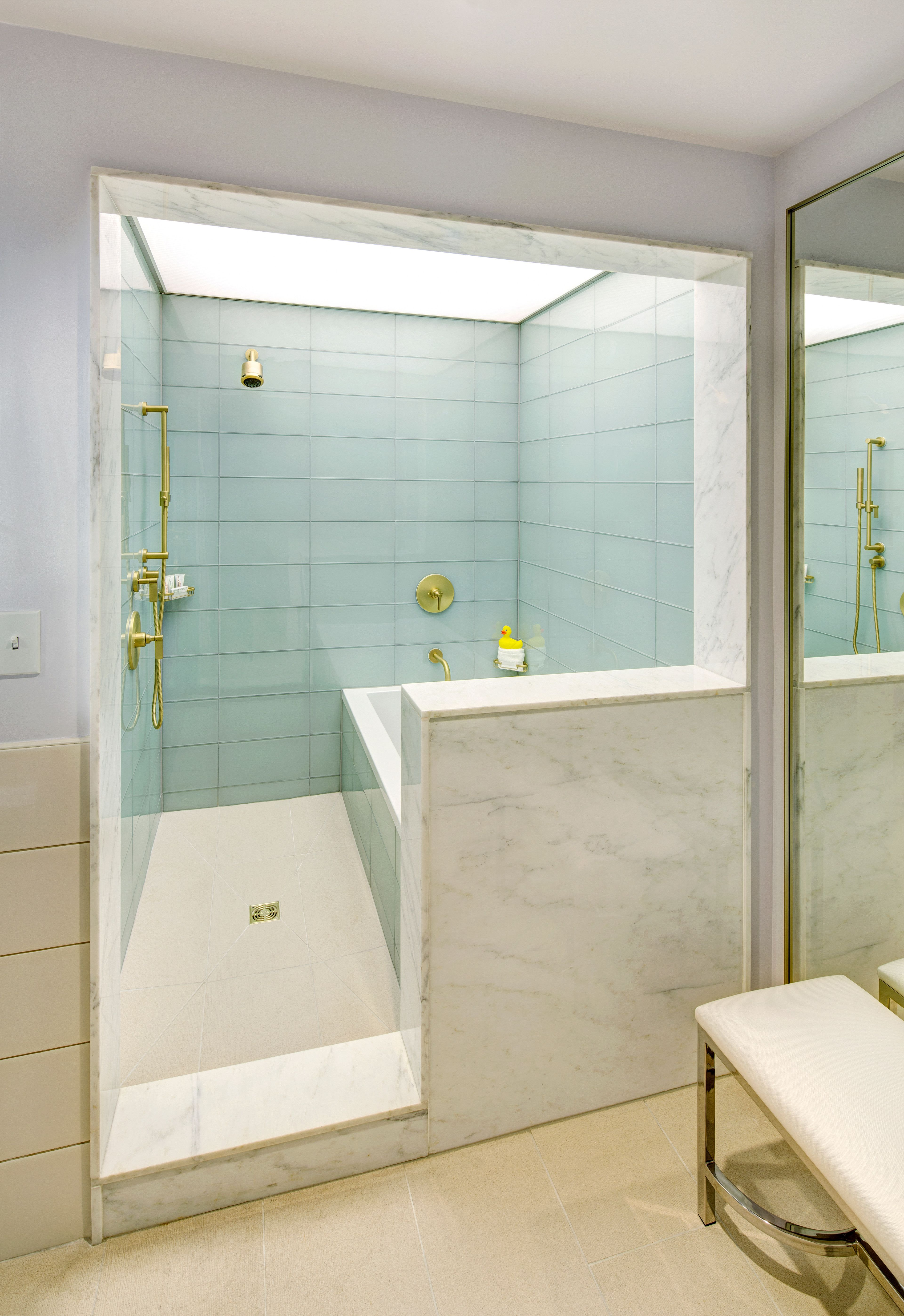 Large-scale glass tile lines the shower enclosure in the suite ...