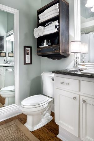 White cabinets, grey/green walls, dark granite on counter, wood tiles ( Homedepot) white marble tub surround, dark shelves/framed mirror, silver/crystal accents