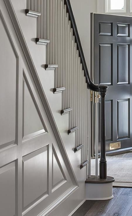 A Staircase Wall With Gray Wainscoting Features Black Handrail White Wood Spindles Around Dark