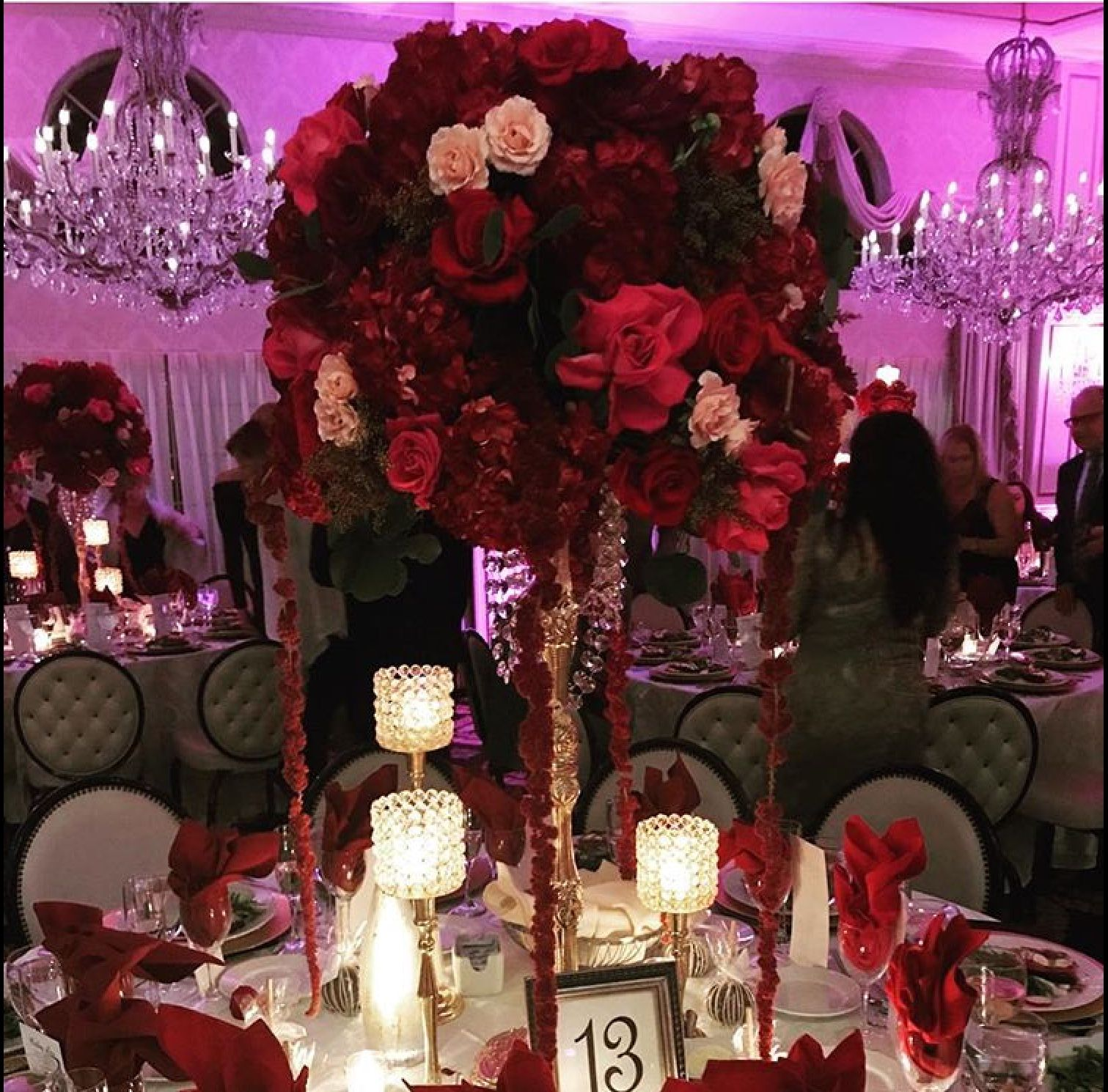Elevated centerpiece with red, hot pink, pink roses with hanging red ...