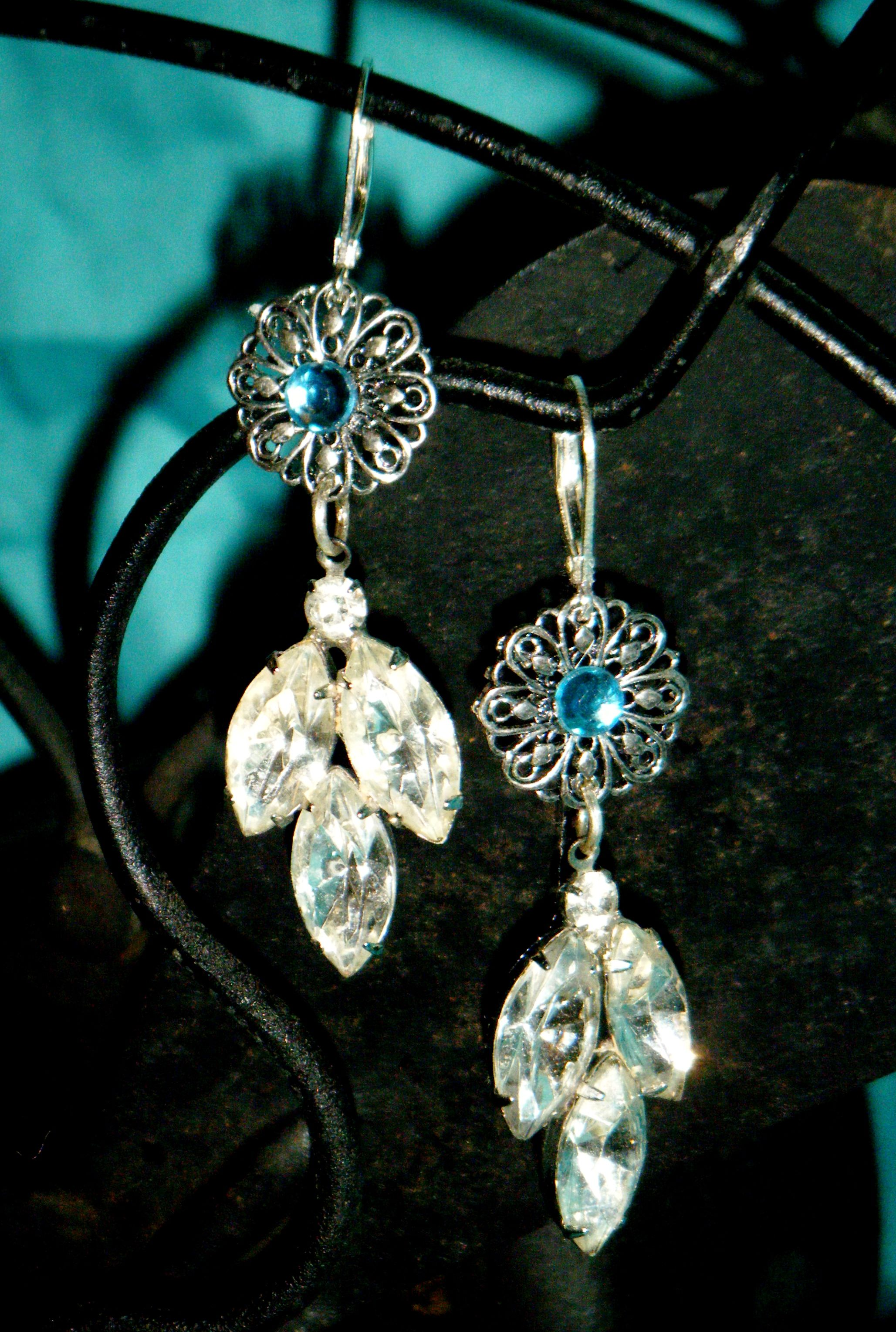 Vintage clip-on earring pieces added on to silver toned metal stampings with blue rhinestone centers, on sterling silver leverbacks