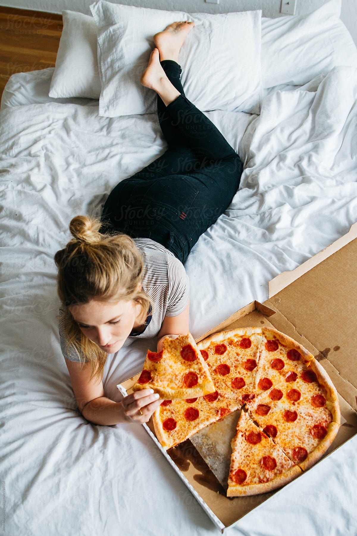 Young Female Laying On Bed Eating Full Pizza Indoors Woman