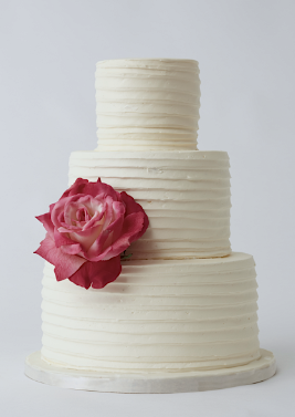 alternate wedding cake design simple textured buttercream icing and a single garden rose in