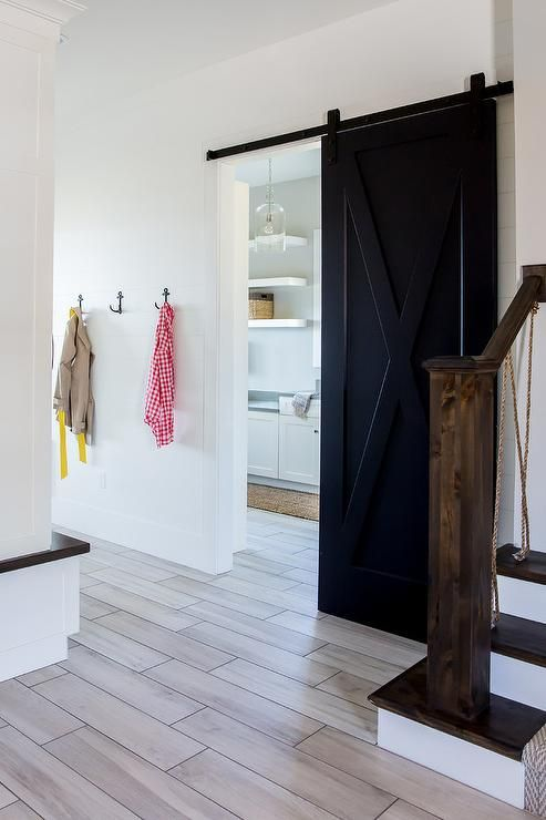 Wood Like Floor Tiles Lead To A Black Barn Door On Rails Opening To A White Laundry Room And Positi Interior Barn Doors Modern Closet Doors White Laundry Rooms