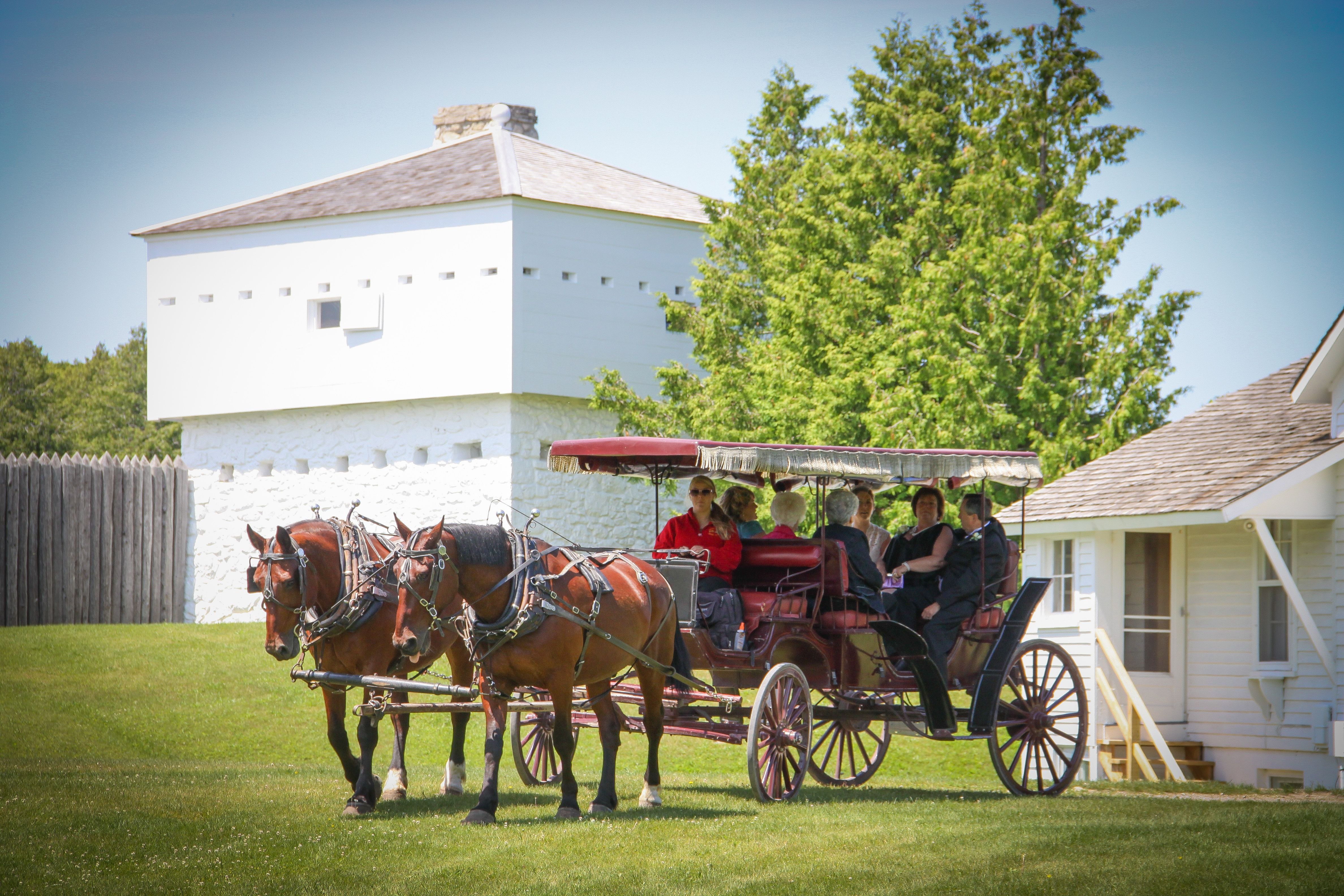 Arriving at the Somewhere In Time Gazebo by a horse-drawn carriage, with the block house from Fort Mackinac behind.