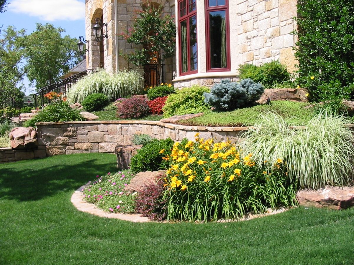 beautiful cobblestone siding sloped landscaping and