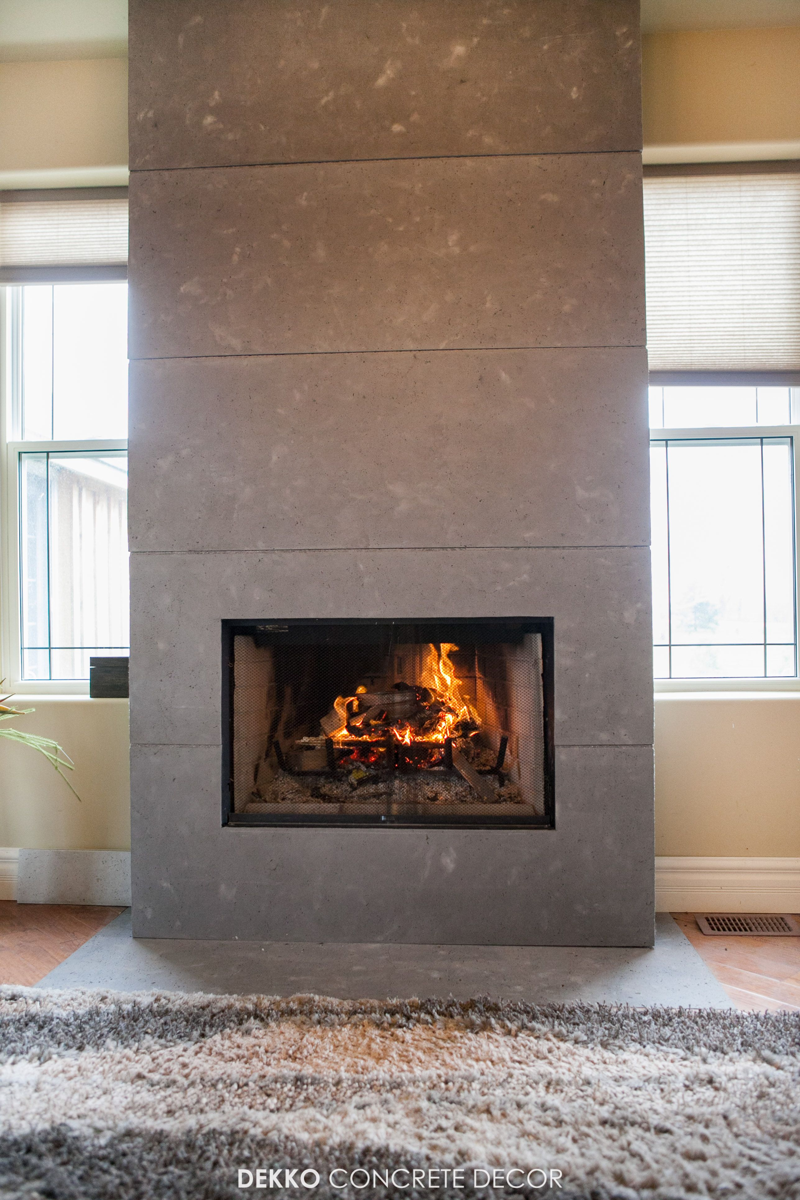 Engineered concrete panels around wood fireplace feature ...