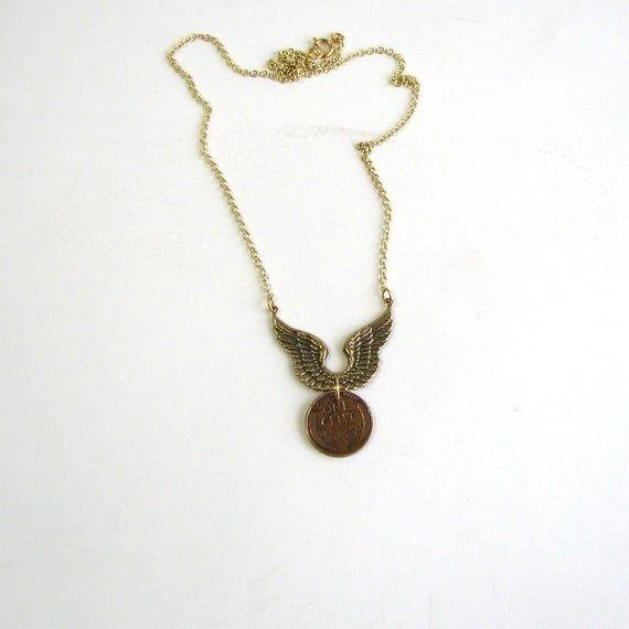 Photo of fliegende Weizen Penny Halskette mit goldenen Flügeln. Viel Glück beim Fliegen / Reisen
