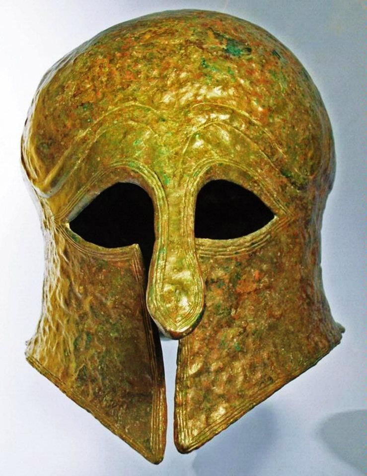 Greek bronze helmet of the Corinthian type, c. 550-500 BCE with a rounded crown and sweeping neck guard, thick elongated nose guard, curvilinear eyeholes tapering to a point, large angular cheek pieces, raised eyebrows, and an incised linear border.