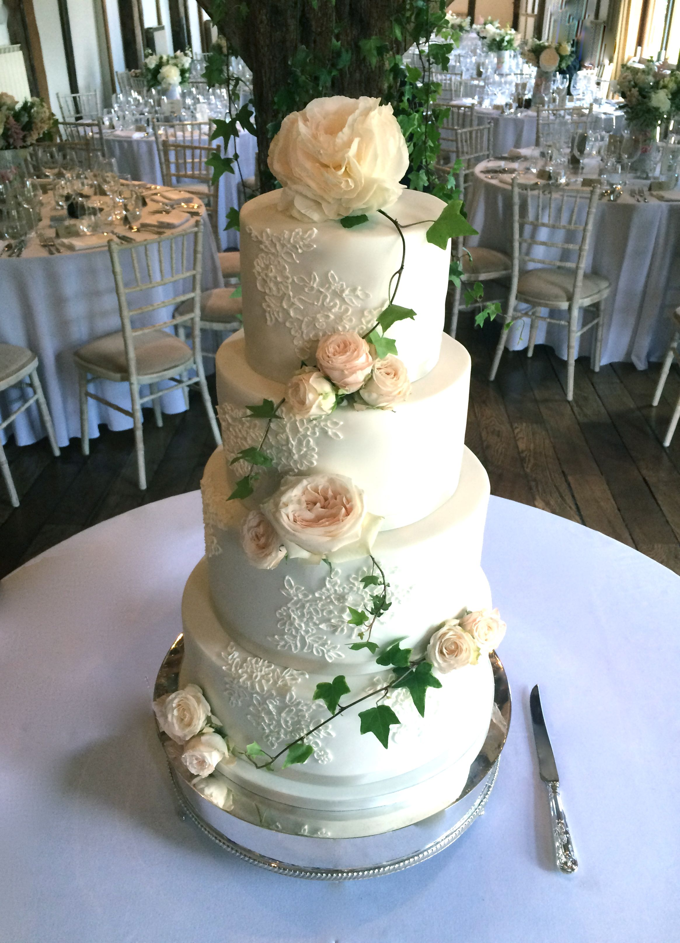 Fresh flower and piped lace wedding cake at loseley park