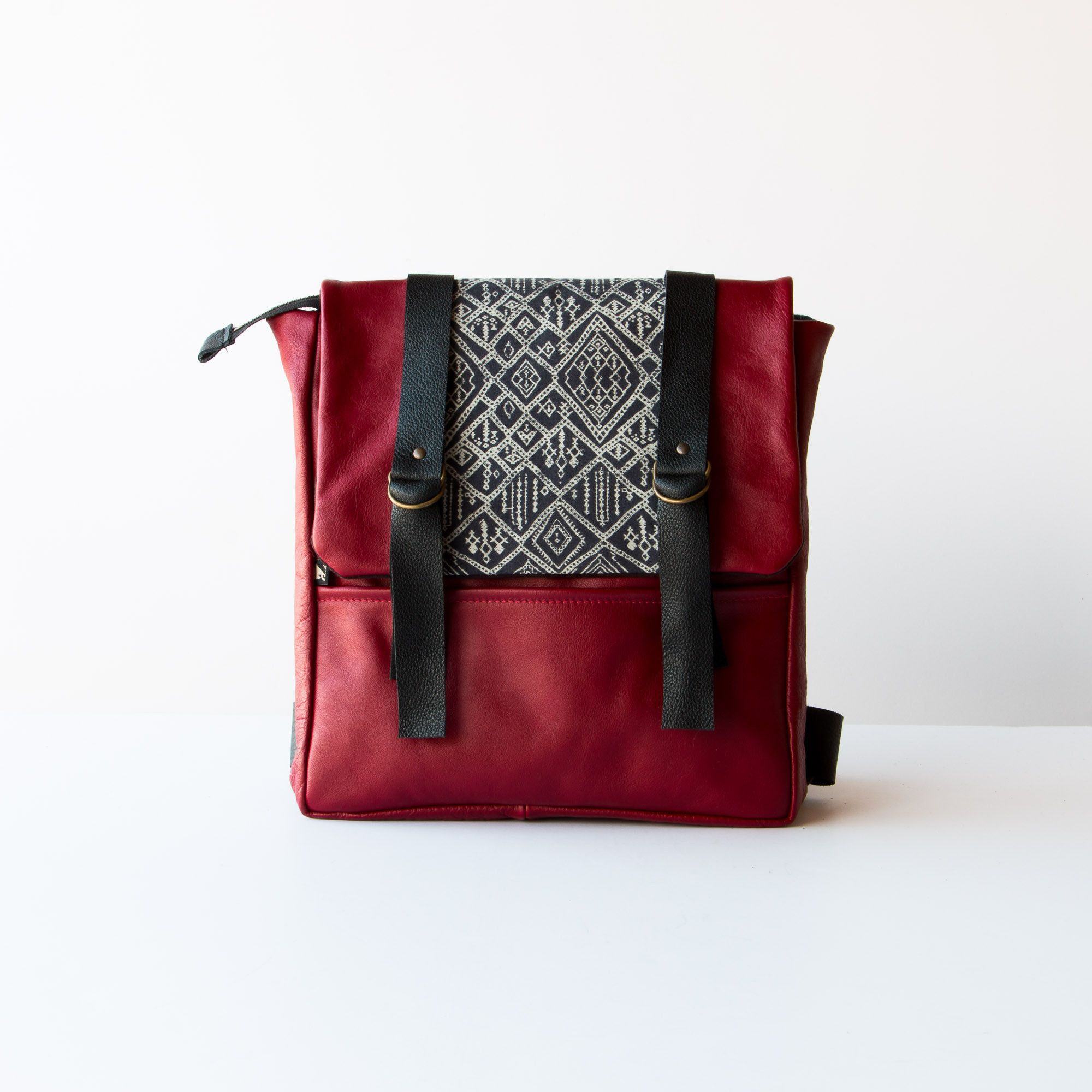 This ravishing backpack is made of recycled leather with a geometric pattern in cotton canvas. It closes with a large clasp and two snaps. It has two pockets: an open pocket inside and a closed pocket with a zipper on the outside. The backpack is transformed into a shoulder bag thanks to its press button system.