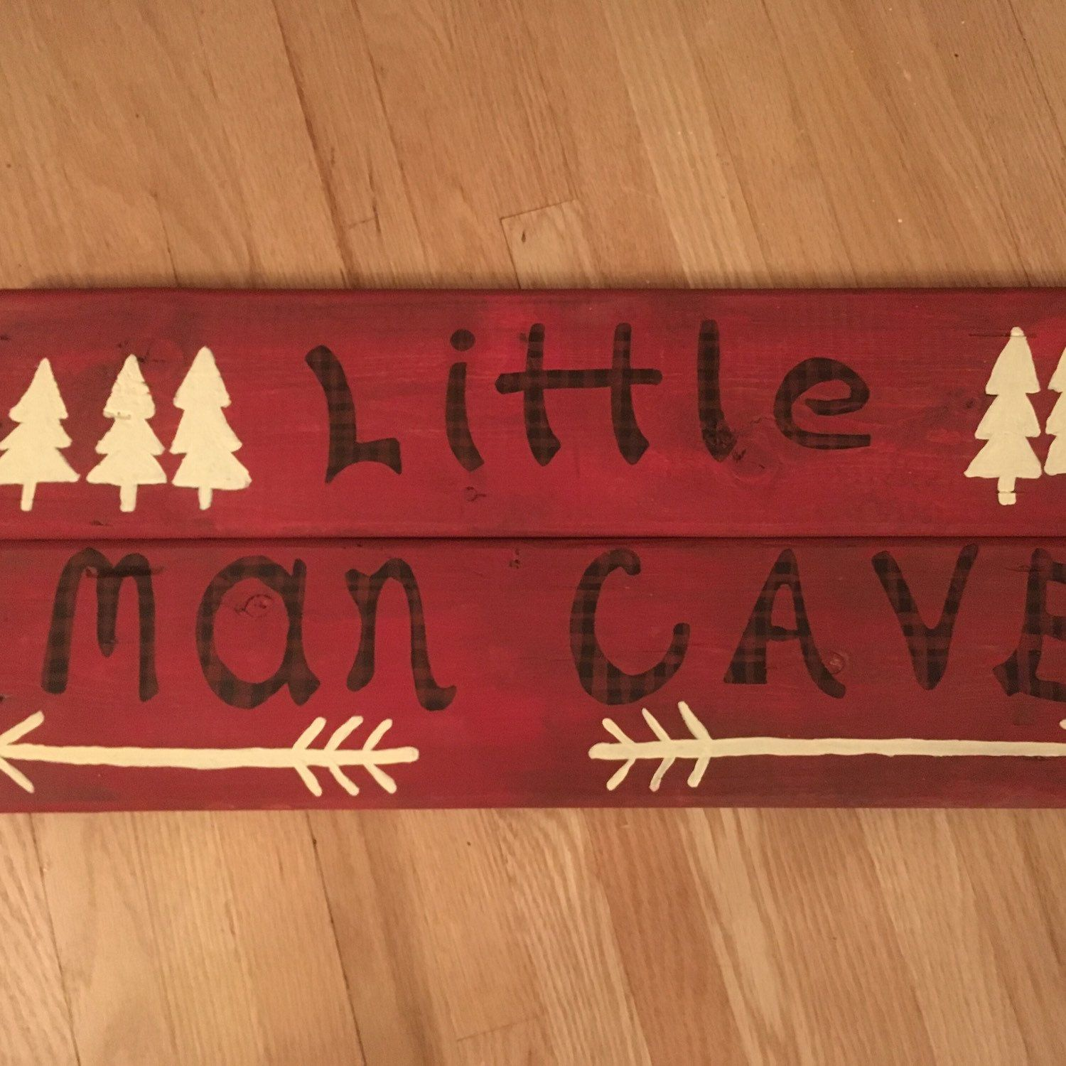 "Little Man Cave  Our newest addition for your newest addition!! The little man cave lumberjack style sign for baby's nursery room. Black and red plaid font with cream colour nature trees &arrows on red distressed reclaimed wood. Size is approx 24"" x 10"""