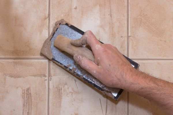 Grout haze is caused when tile is installed and the grout is not completely removed from the tile surface after the project is completed.