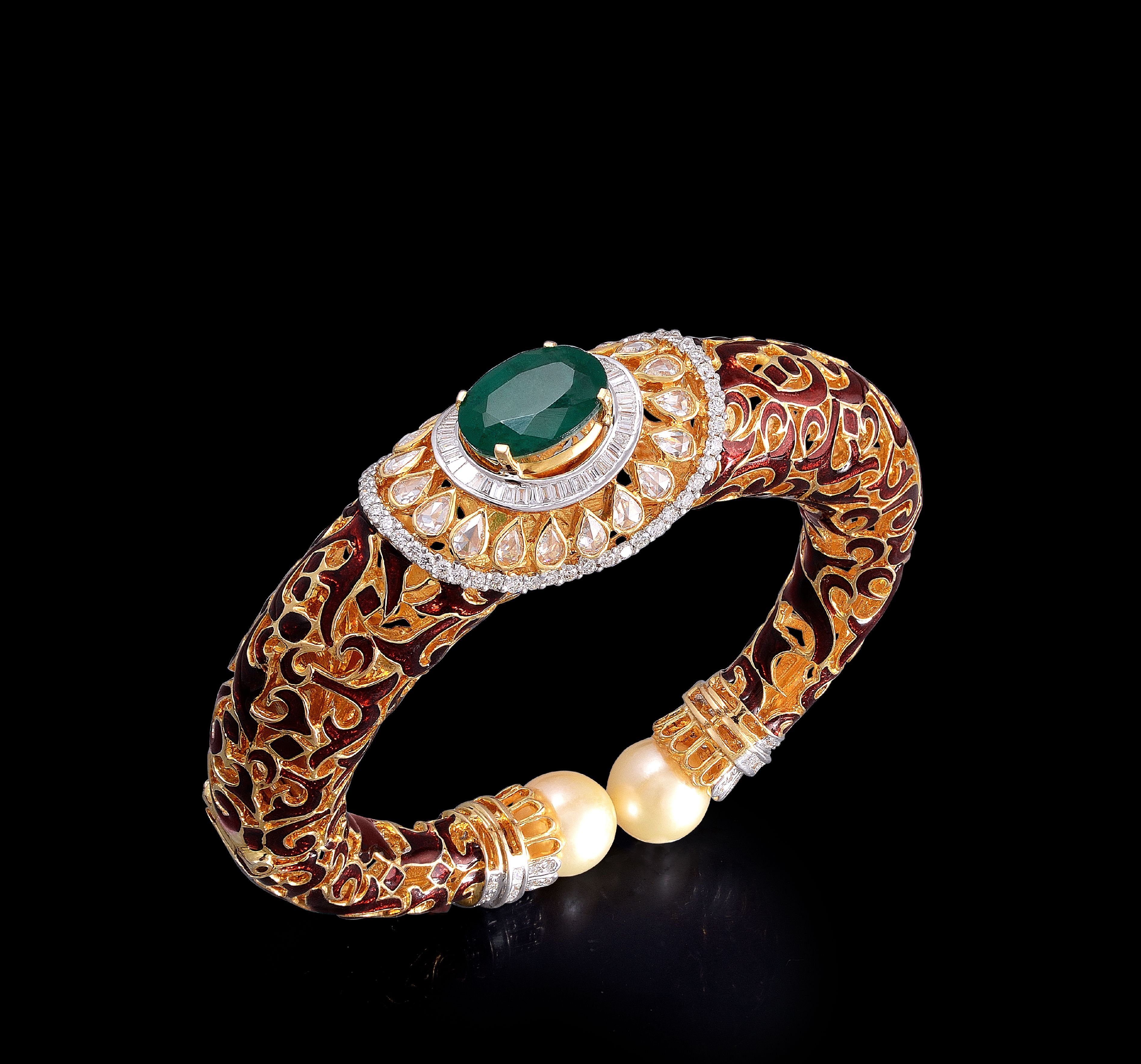Beautiful gold and diamond kada with an alluring emerald by