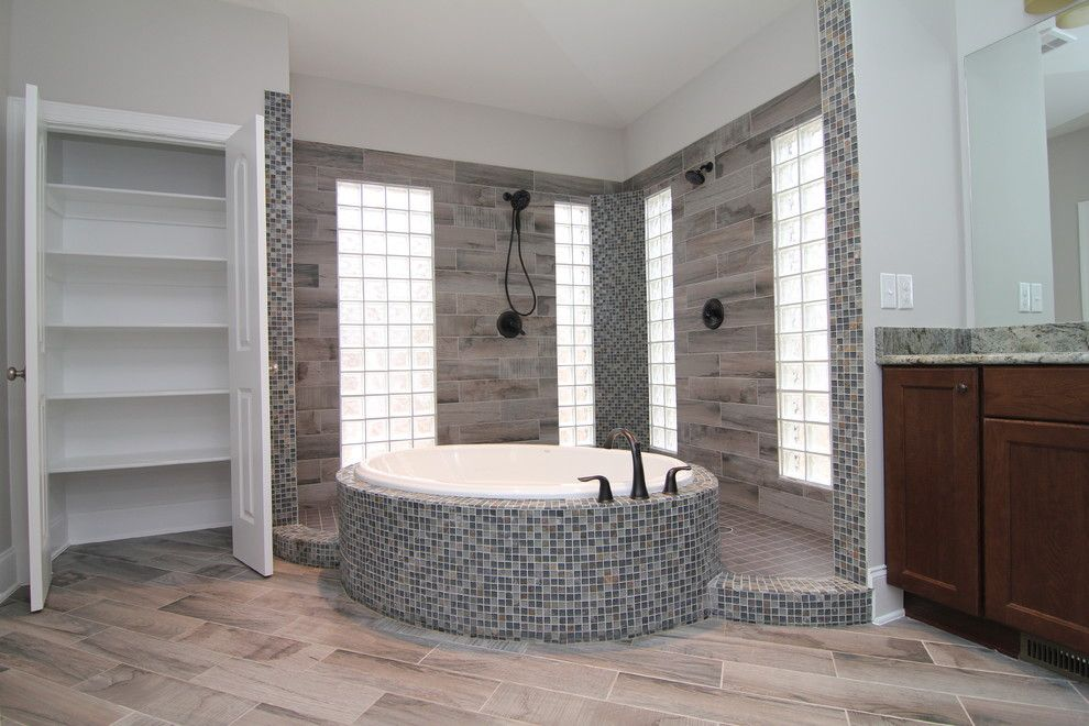 A Wide Open Tile Shower With Tub Inside Is The Centerpiece Of This Master  Suite Bath. Mini Mosaic Tiles Are Paired With Extra Long Faux Wood Ceramic  Tiles.