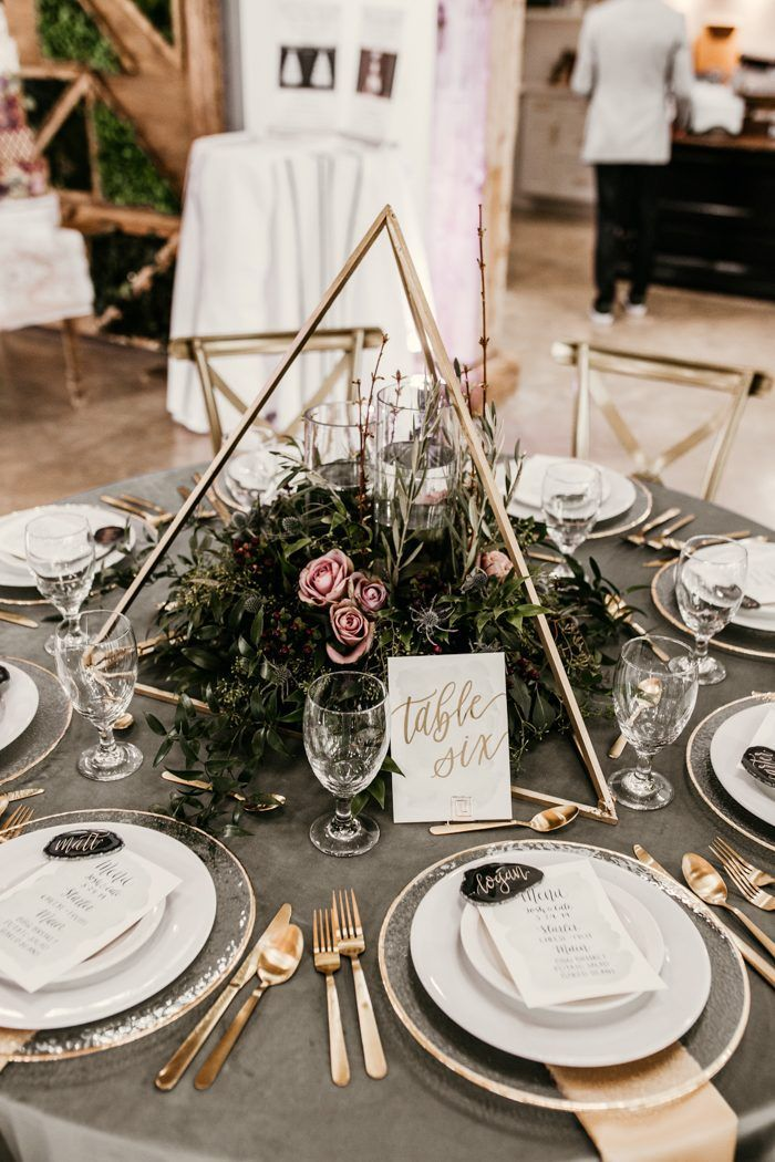 Romantic + modern wedding reception table featuring geometric decor, pink blooms, and gold accents…