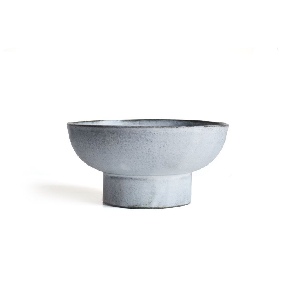 A striking, hand-thrown, sculptural footed ceramic bowl by LA-based designer Eric Roinestad. The bowl is glazed in layered colors of whites, grays, and soft blues. Eric draws inspiration from mixing the organic forms of the Southern California natural landscape and the modern forms of his Scandinavian heritage.