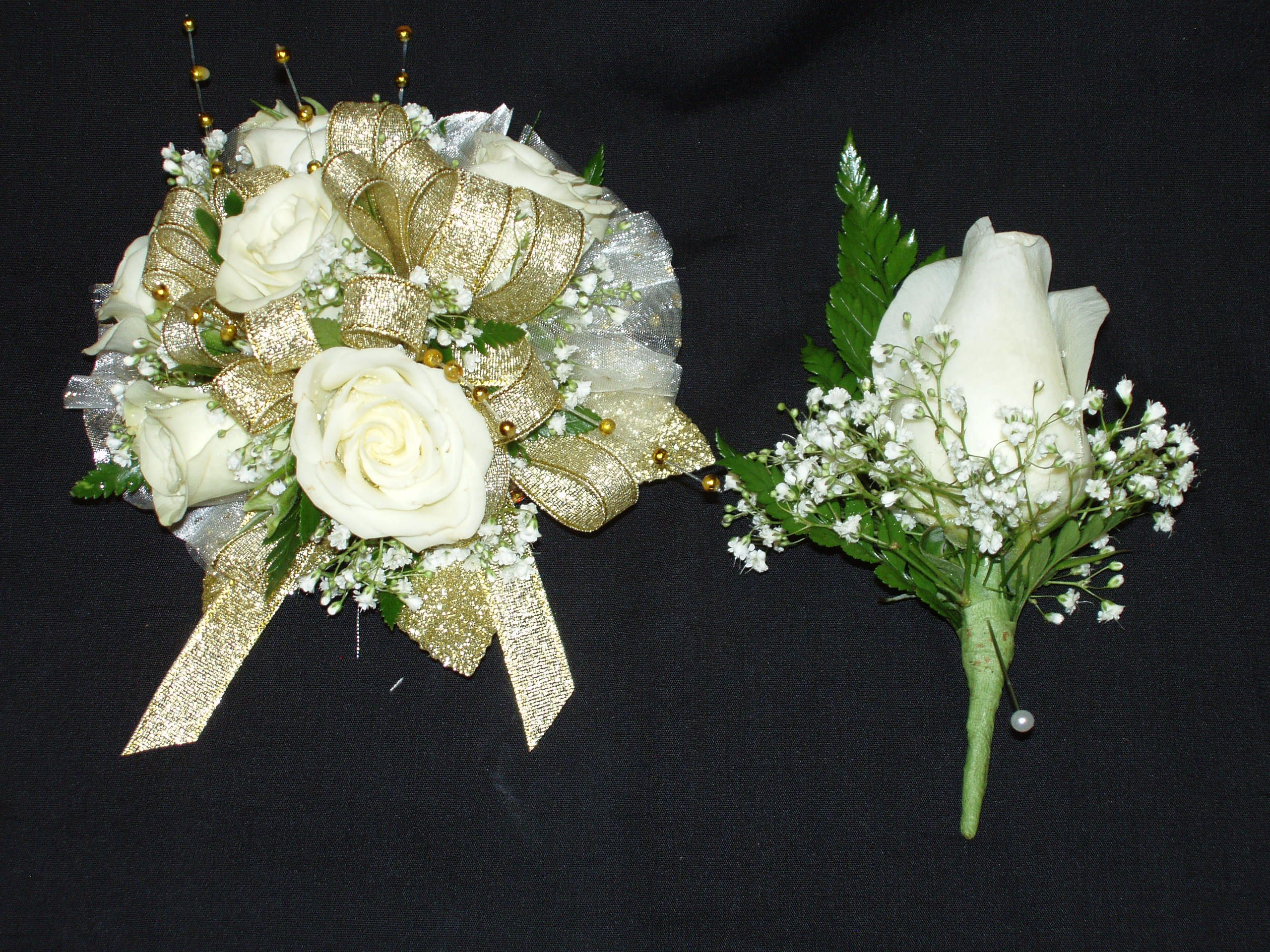 Wrist corsage with white spray roses, gold ribbon and ...