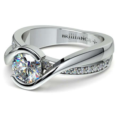 New week, new sparkle: Exude elegance in the sleek beauty and diamond shimmer of the Bezel Diamond Bridge Engagement Ring in durable Platinum, featuring twenty round-cut diamonds in a pave setting accentuating the stunning center!