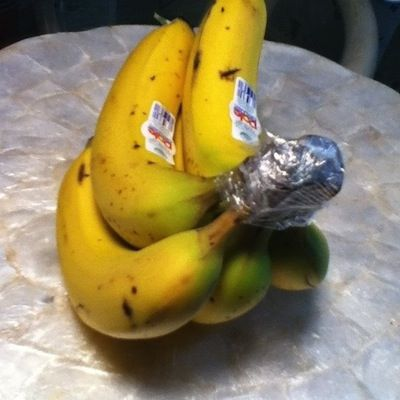 Wrap the crown of a bunch of bananas with plastic wrap.