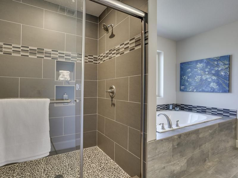 Tile shower with inset shelves & pebble floor. Garden tub with tile ...