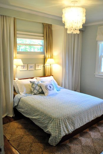 The wardrobe shelves flanking the bed at Young House Love add character and interest to the formerly flat wall behind the bed in this bedroom, along with extra closet space.  The inexpensive shelves fake the look of real built-ins with the addition of molding and pretty fabric fronts.