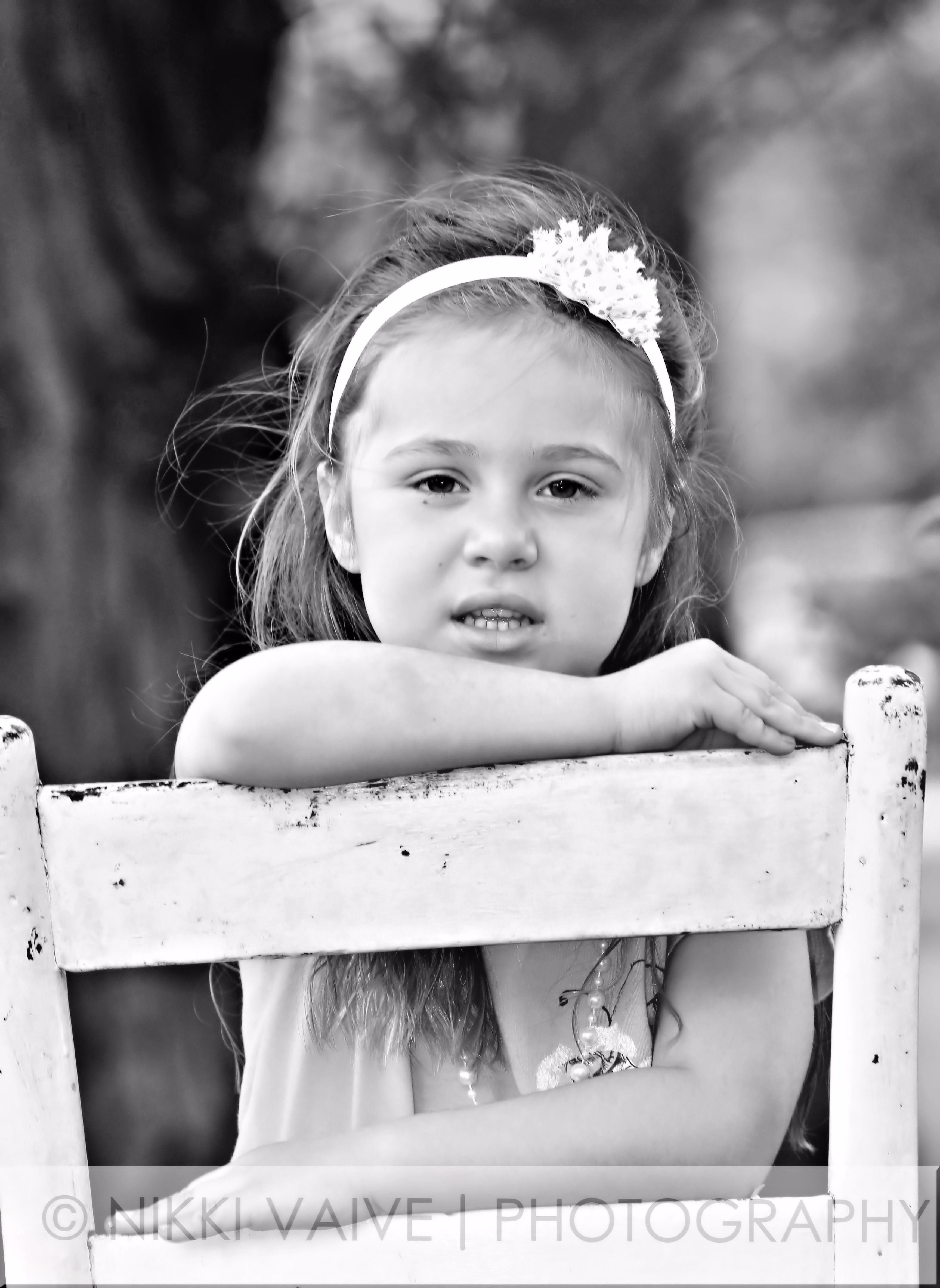 Childrens portraits girl serious pose seated in chair in the