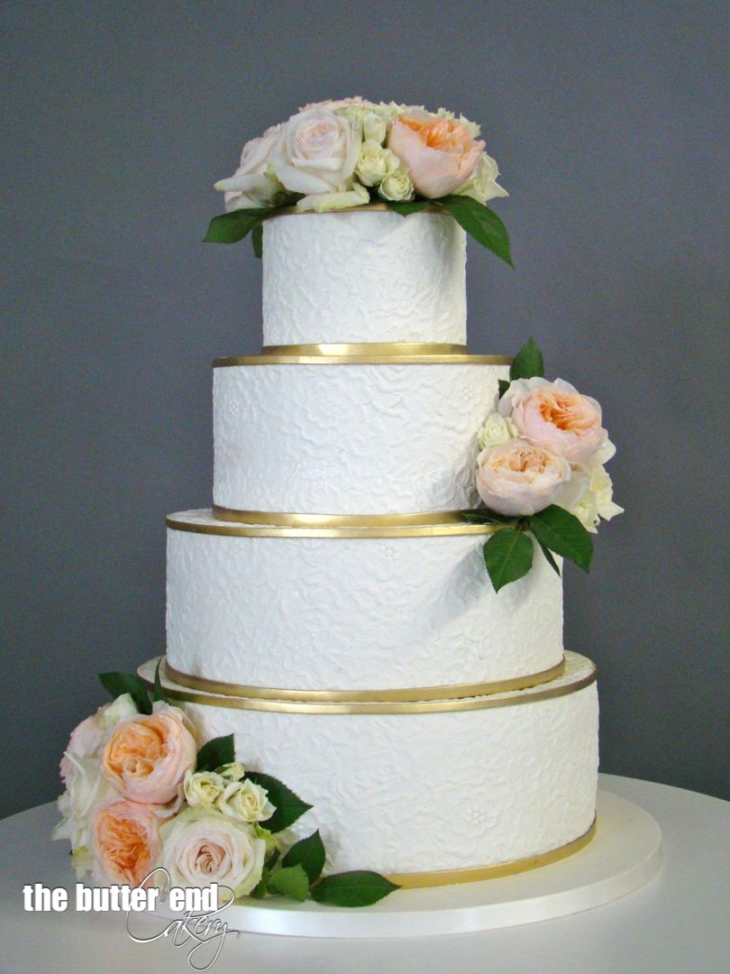 White and gold embossed wedding cake with fresh flowers by The ...