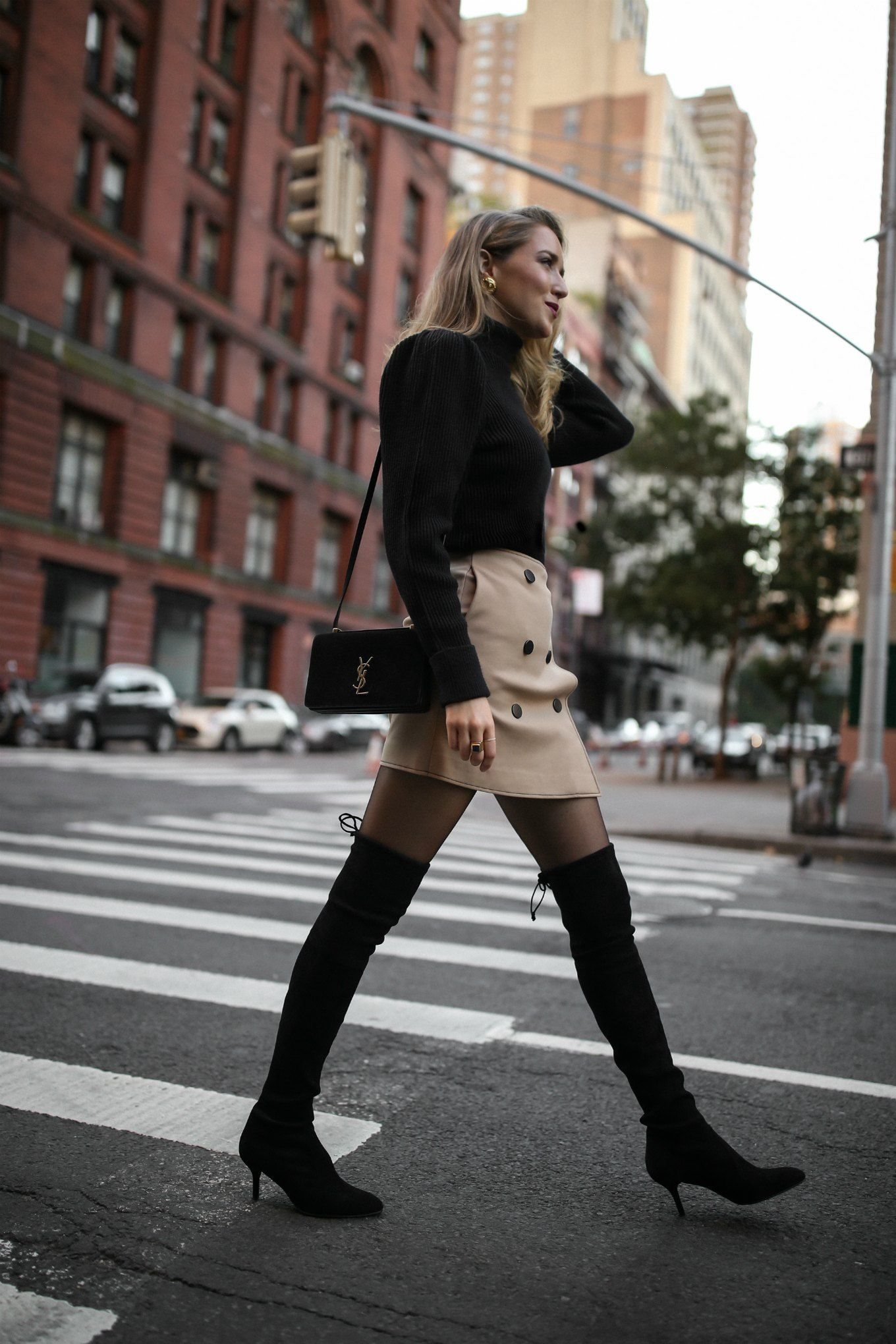5b59b7e8a9bf Mary Orton wears a black puffed-shoulder turtleneck, a khaki mini skirt and  black Stuart Weitzman over-the-knee boots