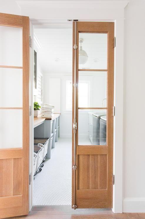 Bi Fold Cremone Bolt Doors Open To A Laundry Room Featuring Rejuvenation 2 1 2 Bushel Steele Canvas Laundry Bins Laundry Room Laundry Room Doors Kitchen Doors
