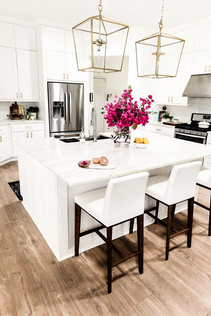 White kitchen with marble countertops and gold light fixtures ...