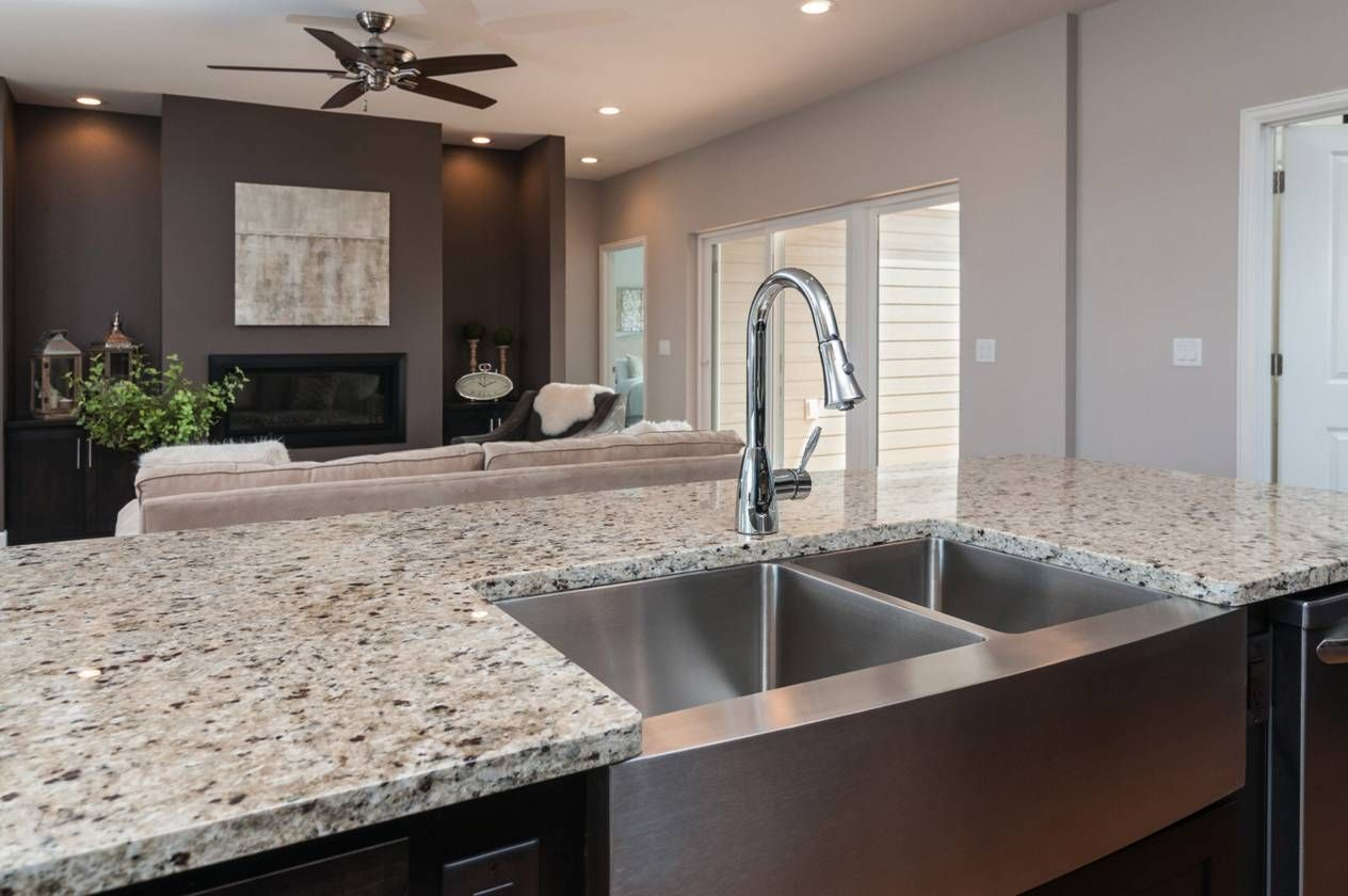 Superbe Kitchen Island With Stainless Farmhouse Sink And Crema Pearl Granite  Countertops.